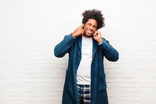 Jonge zwarte man met pyjama met jurk op zoek boos, gestrest en geërgerd, die beide oren bedekt met een oorverdovend geluid, geluid of luide muziek