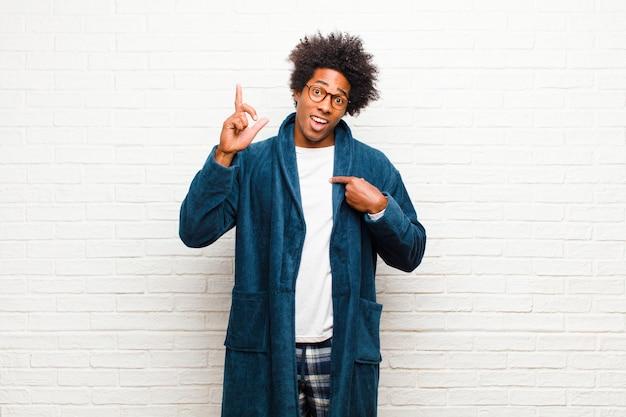 Jonge zwarte man met pyjama met jurk trots en verrast voelen, wijzend op zelfverzekerd, gevoel als succesvol nummer één