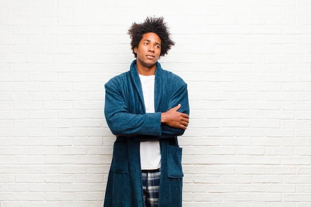 Jonge zwarte man met pyjama met jurk twijfelen of denken, lip bijten en zich onzeker en nerveus voelen, op zoek naar copyspace aan de zijkant tegen baksteen