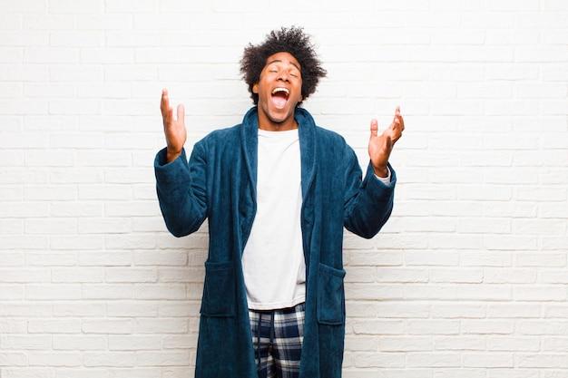 Jonge zwarte man met pyjama met jurk woedend schreeuwen, gestrest en geïrriteerd voelen met handen omhoog in de lucht zeggen waarom ik