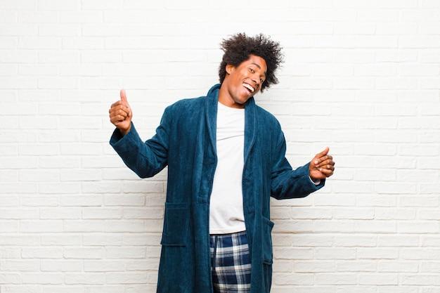 Jonge zwarte man met pyjama met toga glimlachen, zorgeloos, ontspannen en gelukkig voelen, dansen en luisteren naar muziek, plezier maken op een feestje tegen de muur