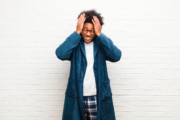 Jonge zwarte man met pyjama's met een jurk die zich gestrest en angstig, depressief en gefrustreerd voelt met hoofdpijn, beide handen ophef