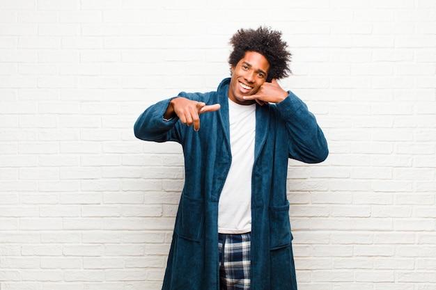 Jonge zwarte man met pyjama's met jurk vrolijk glimlachen en wijzend naar de camera terwijl u belt later gebaar, praten over telefoon tegen baksteen