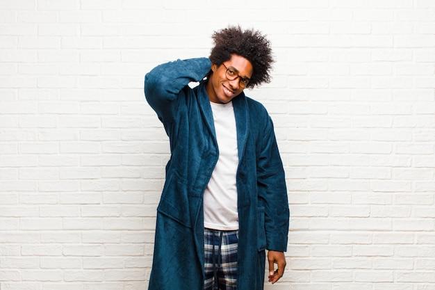 Jonge zwarte man met pyjama's met toga vrolijk en vol vertrouwen lachen met een ongedwongen gelukkig vriendelijke glimlach tegen bakstenen muur