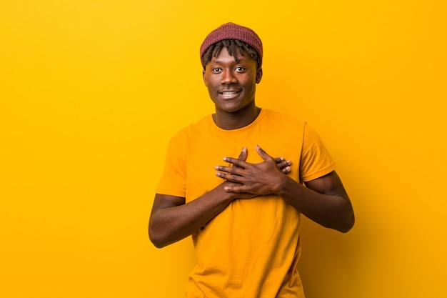 Jonge zwarte man met rasta's op geel heeft vriendelijke uitdrukking en drukt met de handpalm tegen de borst. liefde concept.