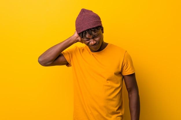 Jonge zwarte man met rasta's op geel lijden nekpijn als gevolg van sedentaire levensstijl.