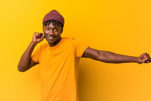 Jonge zwarte man met rasta's over gele muur dansen en plezier maken.