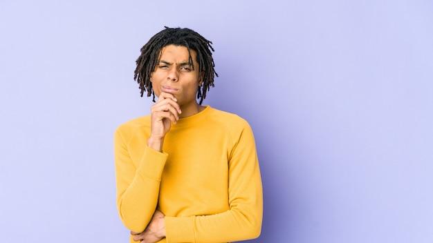 Jonge zwarte man met rastakapsel denken en opzoeken, reflecterend zijn, contempleren, een fantasie hebben.