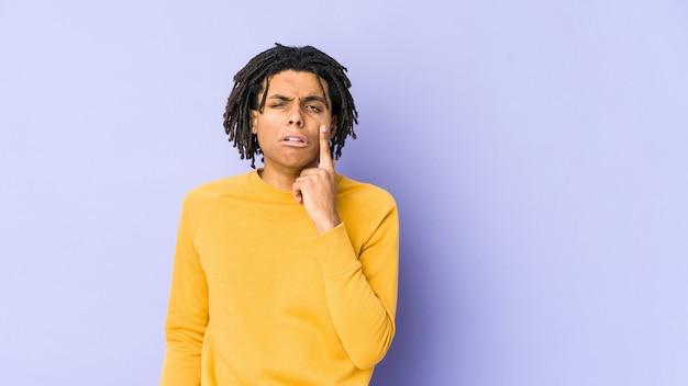 Jonge zwarte man met rastakapsel huilen, ongelukkig met iets, pijn en verwarring concept.