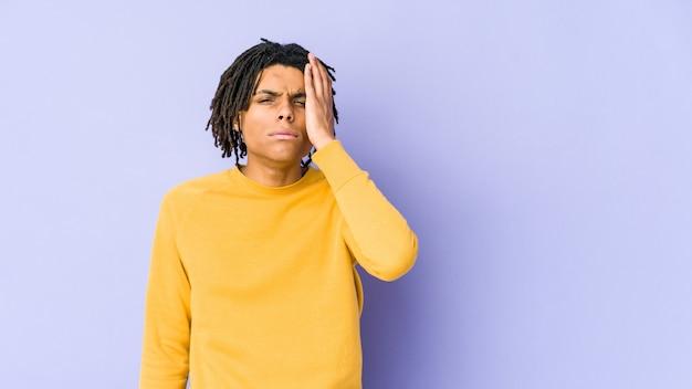 Jonge zwarte man met rastakapsel moe en erg slaperig hand op het hoofd houden.