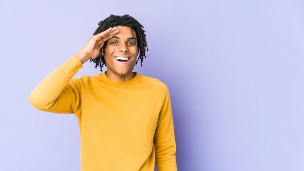 Jonge zwarte man met rastakapsel schreeuwt luid, houdt ogen open en handen gespannen.