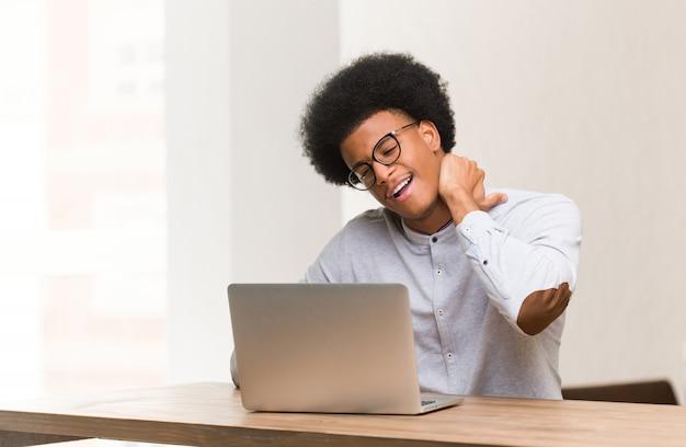 Jonge zwarte man met zijn laptop die lijdt aan nekpijn