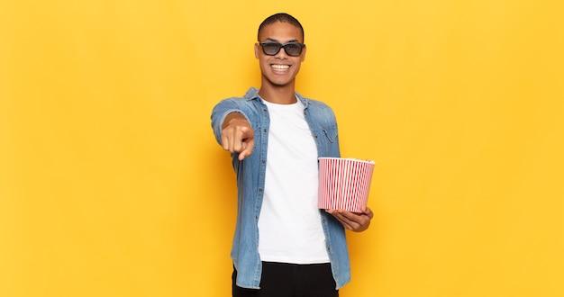Jonge zwarte man naar voren wijzend met een tevreden, zelfverzekerde, vriendelijke glimlach, die jou kiest