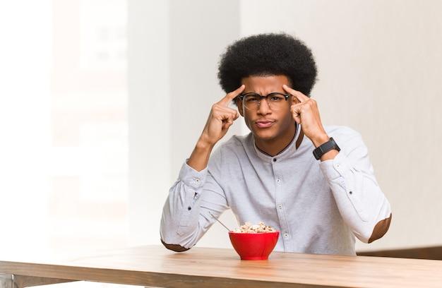 Jonge zwarte man ontbijten doet een gebaar van concentratie