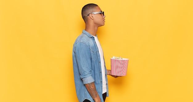 Jonge zwarte man op profielweergave die ruimte vooruit wil kopiëren, denken, zich voorstellen of dagdromen