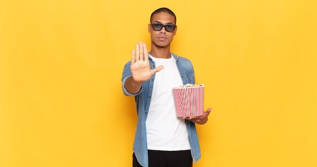 Jonge zwarte man op zoek ernstig, streng, ontevreden en boos met open palm stop gebaar maken