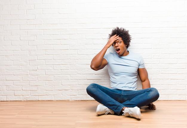 Jonge zwarte man op zoek gelukkig, verbaasd en verrast, glimlachend en het realiseren van geweldig en ongelooflijk goed nieuws zittend op de vloer thuis