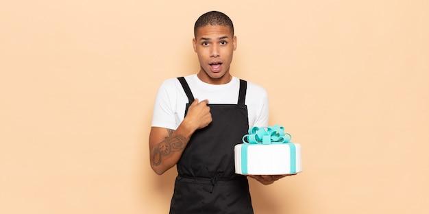 Jonge zwarte man op zoek geschokt en verrast met wijd open mond, wijzend naar zichzelf