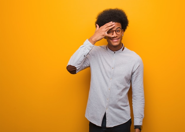 Jonge zwarte man over een oranje muur beschaamd en tegelijkertijd lachen