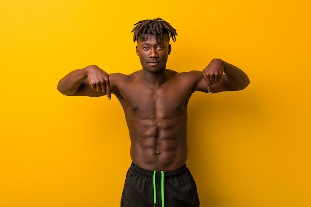 Jonge zwarte man shirtless dragen badpak wijst naar beneden met vingers, positief gevoel.