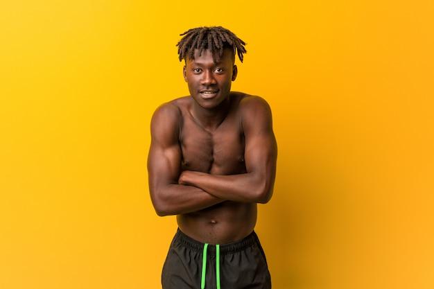 Jonge zwarte man shirtless dragen zwembroek lachen en plezier maken.