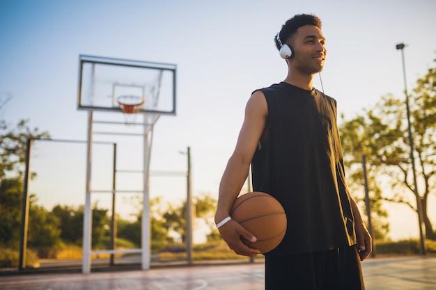 Jonge zwarte man sport doen, basketbal spelen op zonsopgang, luisteren naar muziek op koptelefoon, actieve levensstijl, zomerochtend