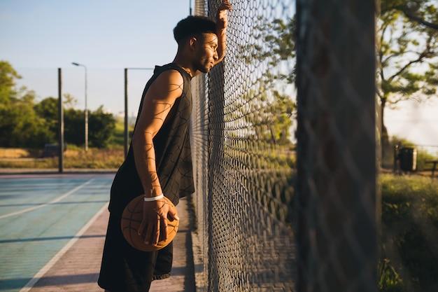 Jonge zwarte man sporten, basketbal spelen op zonsopgang, actieve levensstijl, zomerochtend
