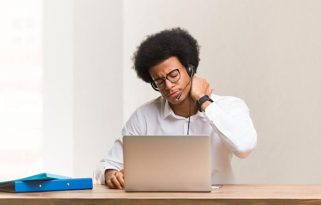 Jonge zwarte man telemarketer die aan nekpijn lijdt