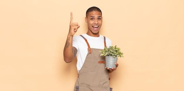 Jonge zwarte man voelt zich een gelukkig en opgewonden genie na het realiseren van een idee, vrolijk vinger opstekend, eureka!