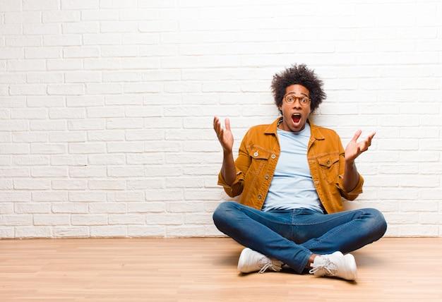 Jonge zwarte man voelt zich extreem geschokt en verrast, angstig en in paniek, met een gestreste en met afschuw vervulde blik thuis op de vloer