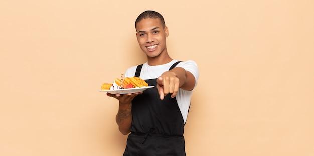 Jonge zwarte man wijst met een tevreden, zelfverzekerde, vriendelijke glimlach, voor jou kiezen