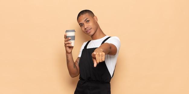 Jonge zwarte man wijzend op de camera met een tevreden, zelfverzekerde, vriendelijke glimlach, die jou kiest