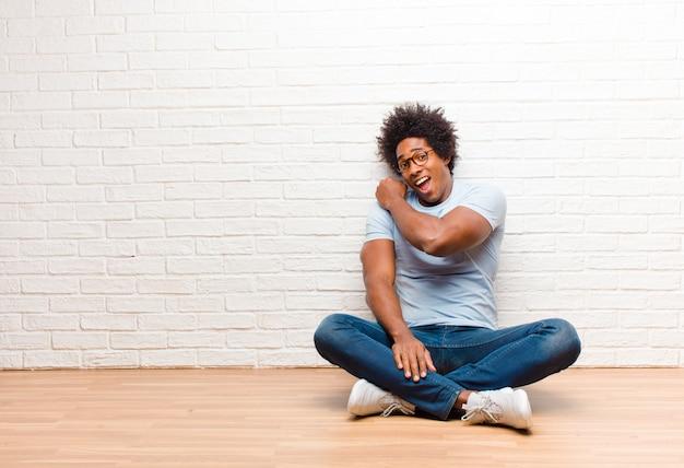 Jonge zwarte man zittend op de vloer met een kopie ruimte