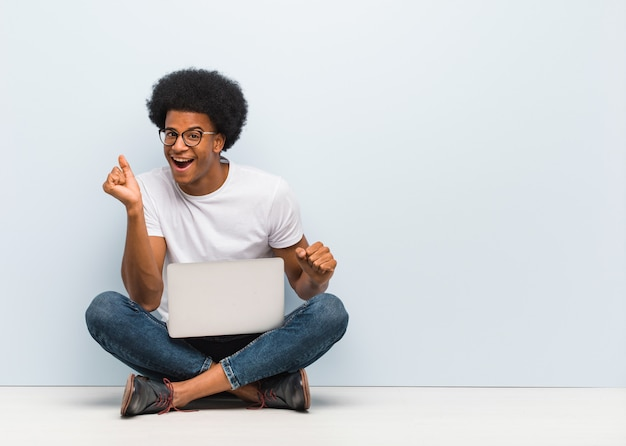Jonge zwarte man zittend op de vloer met een laptop dansen en plezier maken