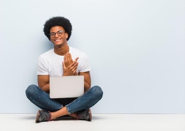 Jonge zwarte man zittend op de vloer met een laptop doet een romantisch gebaar