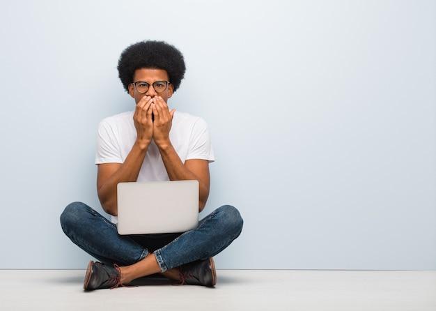 Jonge zwarte man zittend op de vloer met een laptop erg bang en bang verborgen