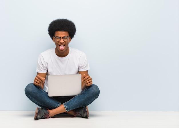 Jonge zwarte man zittend op de vloer met een laptop funnny en vriendelijk tonende tong