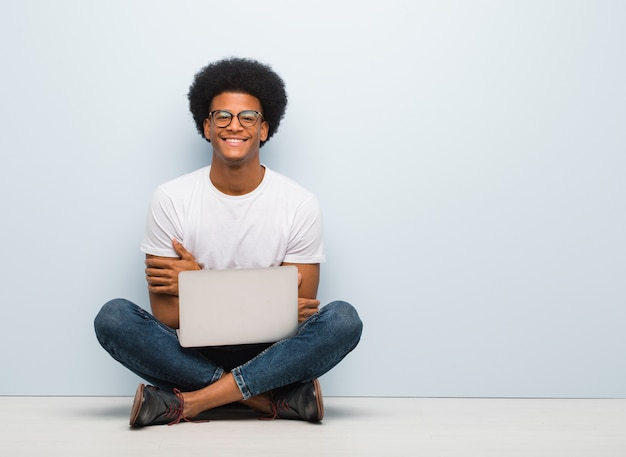 Jonge zwarte man zittend op de vloer met een laptop kruising armen, glimlachend en ontspannen