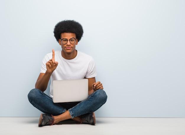 Jonge zwarte man zittend op de vloer met een laptop met nummer één