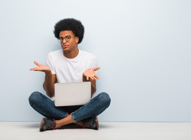 Jonge zwarte man zittend op de vloer met een verward en twijfelachtig laptop