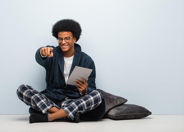 Jonge zwarte man zittend op zijn huis en houdt zijn tablet vrolijk en glimlachend naar voren wijzend