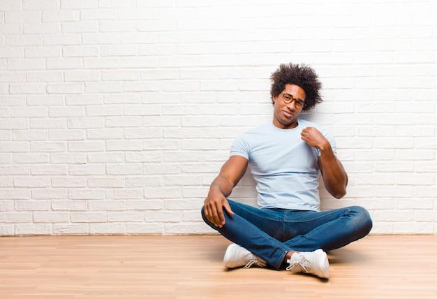 Jonge zwarte mens die arrogant, succesvol, positief en trots kijkt, wijzend op zelf zittend op de vloer thuis