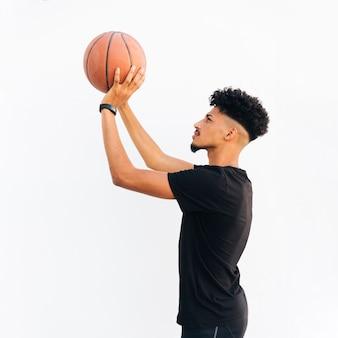 Jonge zwarte mens die basketbal voorbereidingen treft te werpen