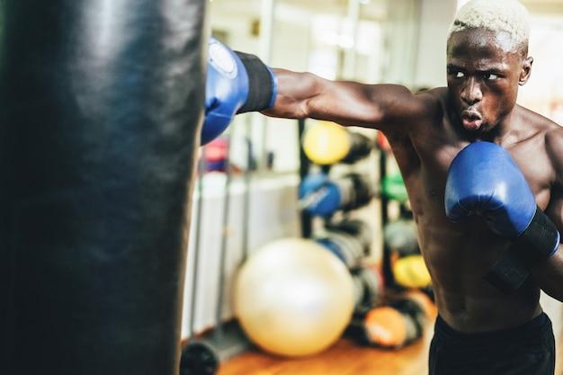 Jonge zwarte mens die binnen de gymnastiekclub van de opleidingsgeschiktheid in dozen doen