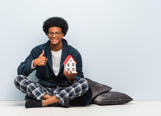 Jonge zwarte mens die een huis modelzitting op de vloer houdt die en duim glimlacht opheft