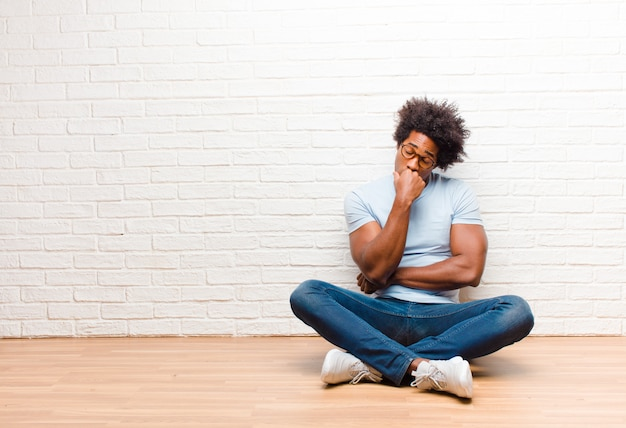 Jonge zwarte mens die ernstig, nadenkend en bezorgd voelt, zijdelings starend met hand die tegen kinzitting op de vloer wordt gedrukt thuis