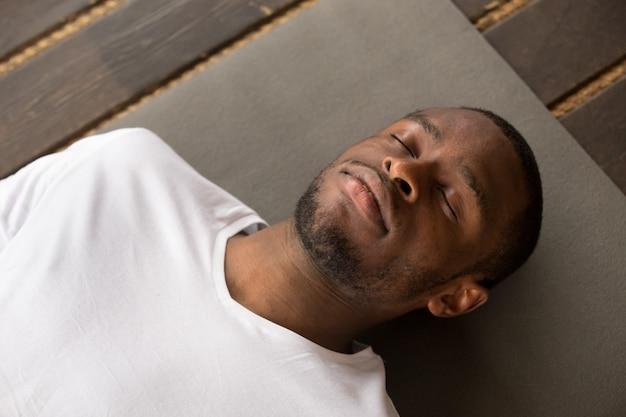Jonge zwarte mens die in lijk lichaamsoefening ligt