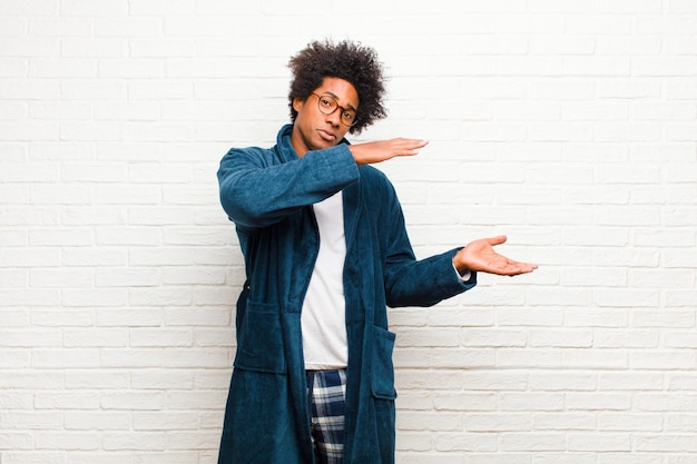Jonge zwarte mens die pyjama's met toga draagt die een voorwerp met beide handen op zijexemplaarruimte houden, een voorwerp tonen, aanbieden of adverteren