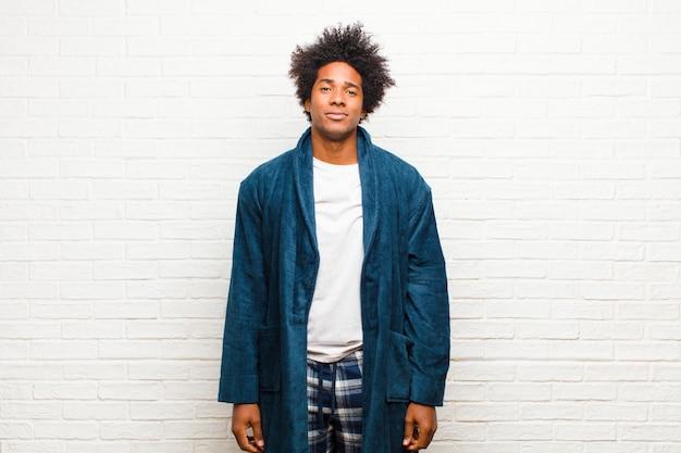 Jonge zwarte mens die pyjama's met toga dragen die positief en vol vertrouwen glimlachen, tevreden, vriendschappelijk en gelukkig tegen bakstenen muur kijken