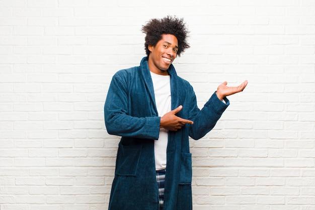 Jonge zwarte mens die pyjama's met toga dragen die trots en vol vertrouwen glimlachen, gelukkig en tevreden voelen en een concept op exemplaarruimte tonen